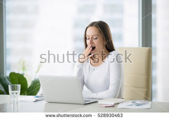 stock-photo-young-business-woman-yawning-at-a-modern-office-desk-in-front-of-laptop-covering-her-mouth-out-of-528930463.jpg